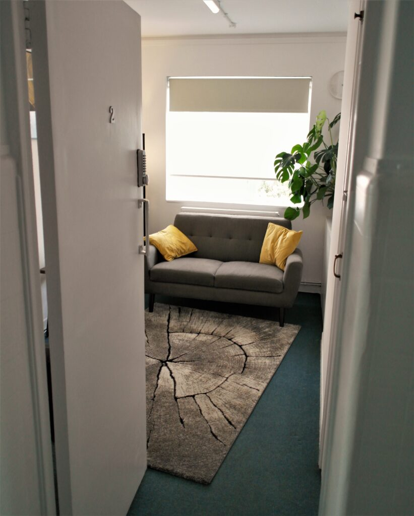 Therapy Room. An open door revealing a welcoming room with a sofa.