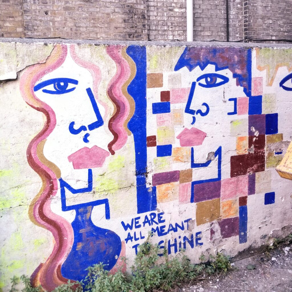 Photograph of grafitti: Two faces with the caption 'We are all meant to shine'